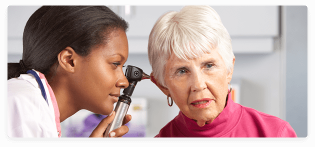 audiologist conducting a hearing check on an old lady
